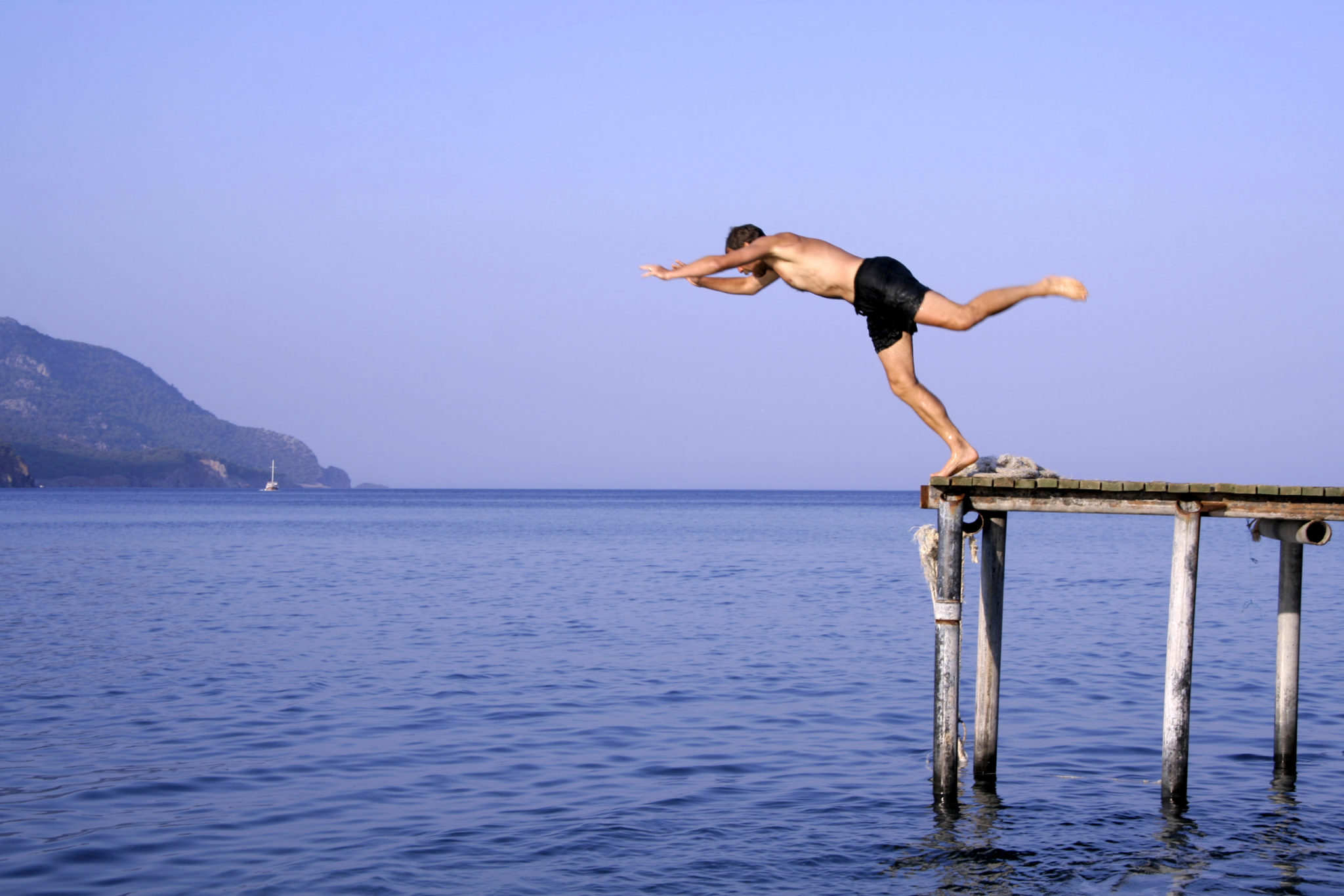 man jump diving from pier into sea